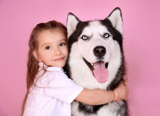 Cute little girl with Husky dog on color background