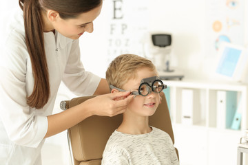 Ophthalmologist examining vision of little child in clinic