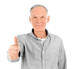 Attractive mature man showing thumb up gesture on white background