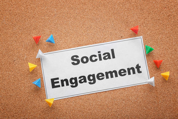Sheet of paper with text SOCIAL ENGAGEMENT on cork background
