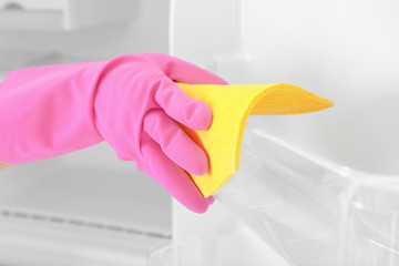 Person washing refrigerator with rag, closeup