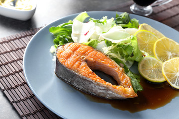 Tasty rainbow trout steak with garnish and sauce on plate