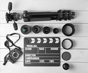 Composition with movie clapper, tripod, camera and different lenses on light background, top view