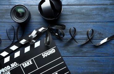 Movie clapper, filmstrip and lenses on wooden background, top view