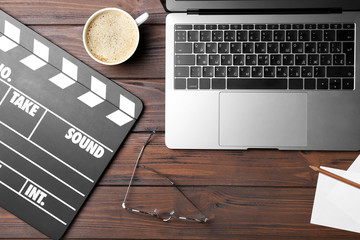 Movie clapper and laptop on wooden background, top view