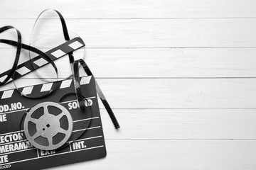 Movie clapper and reel on light background, top view