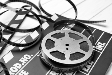 Movie clapper and reel on light background, closeup