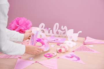Woman preparing decorations for baby shower party on table