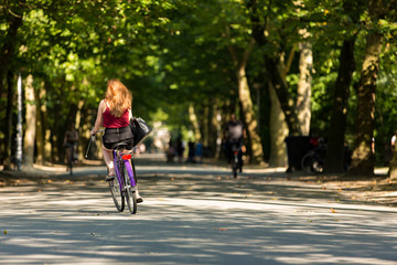 A girl biking in the Amsterdam Vondelpark.