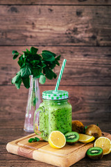 Delicious kiwi smoothie with mint in mason jar on table against dark wooden background. Healthy lifestyle concept