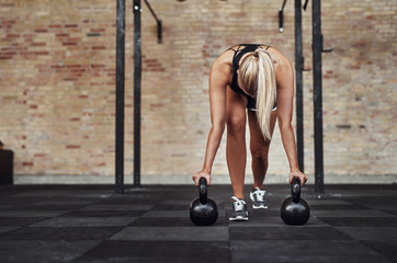 Fit young women weight training alone in a gym
