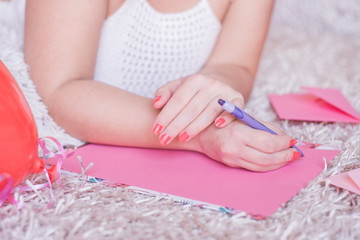 Young woman hands writing a letter for Valentines Day on pink blank paper.