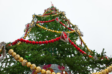 Big Christmas tree with balls and garlands. Bottom view.