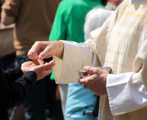 Pfarrer überreicht Hostie beim Abendmahl