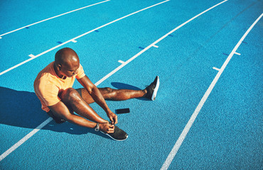 Young athlete tying his shoes before for a track run