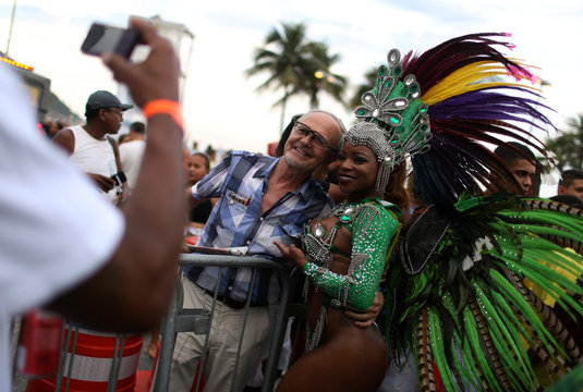 A tourist poses with a dancer for a photo during the gathering of orchestras of samba schools in Copacabana beach in Rio de Janeiro