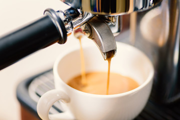 Coffee making, hot coffee flowing into a cup from espresso machine