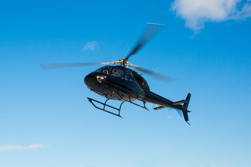 Wall Murals Helicopter solo black helicopter in blue skies