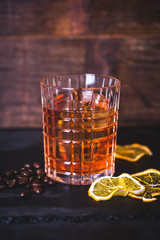A glass with whiskey on a wooden background.