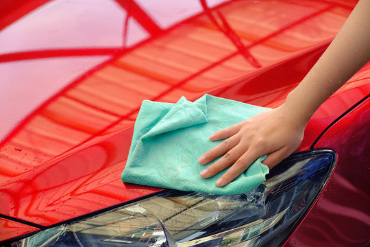 hand women hold water over the red car for washing with microfiber cloth