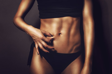 Fitness flat belly woman pinching abs skin