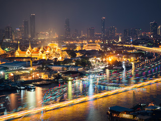 High view of Chaopraya river and light of transportation by boat with Grand Palace and background of high building