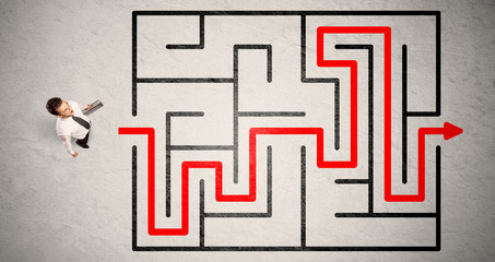Lost businessman found the way in maze with red arrow