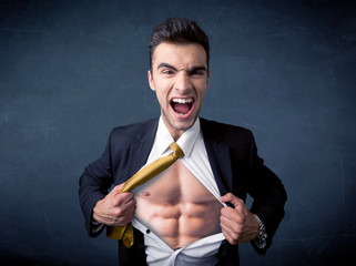 Businessman tearing off shirt and showing mucular body