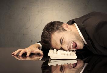 Frustrated businessman's head on keyboard