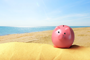 Piggy bank on a beach. Vacation savings concept