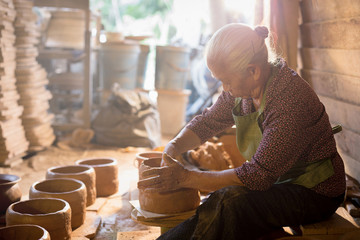 Potter at work. Close-up of woman making ceramic pot on the pottery wheel