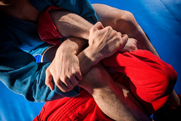 Man wrestlers of grappling and jiu jitsu in a blue and red kimono makes submission wrestling.Fighting techniques:   armbar, armlock
