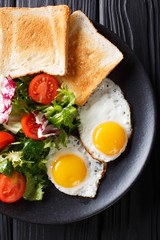 healthy breakfast of fried eggs with fresh vegetable salad and toast close-up. vertical top view