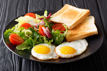 Organic food breakfast: fried eggs with fresh vegetable salad and toast close-up on a plate. horizontal