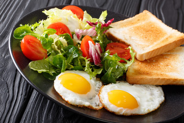 Homemade healthy breakfast: fried eggs with fresh vegetable salad and toast close-up on a plate. horizontal
