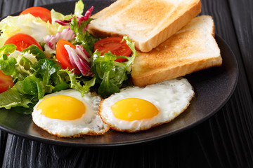fried eggs with fresh vegetable salad and toast close-up. horizontal