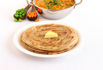 Kerala paratha, a type of Indian bread, with butter topping, and in the background is a wok of peas and carrot curry.