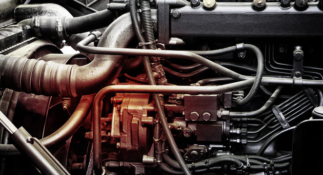 A classic fragment of diesel car engine or truck engine with copy space for text. Metallic background of the internal diesel truck engine or car engine.