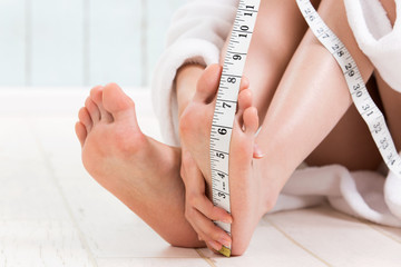 メジャーで足のサイズを測る女性