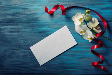 White Orchid and envelope on a blue wooden
