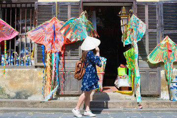 Tourist woman is wearing Non La (Vietnamese tradition hat) and enjoy sightseeing at Heritage village in Hoi An city in Vietnam.