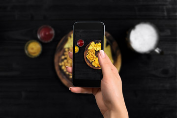Hand's of woman taking picture photo food with mobile smart phone. Top view. Mexican nachos with two kind sauce on photo