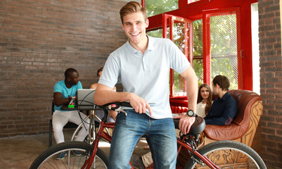Young man sitting on a bicycle in a modern office.