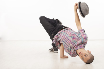 Young male dancer sitting on his head with hat up