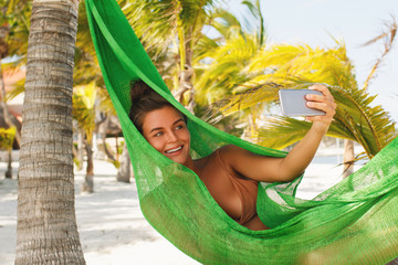 Happy and beautiful woman lying in the hammock
