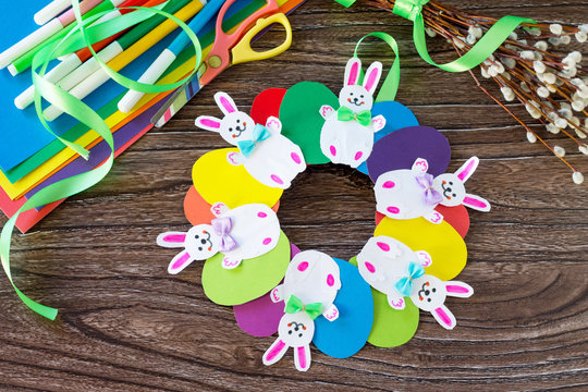 Children's Easter gift wreath with colorful eggs and Easter bunnies.  Paper, scissors, glue on a wooden table.Hand-made. Children's art project for children. Craft for kids.