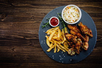 Kentucky wings with French fries wooden background