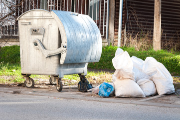 White plastic bags full of garbage on the street near the metal dumpster can littering and polluting the city