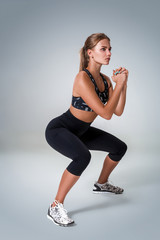 Fitness woman in sports clothing doing sit-ups, studio shot