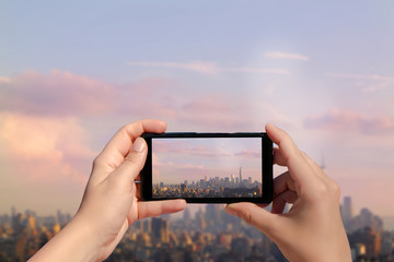 Female hand with mobile phone take picture of midtown of Manhattan on sunset. Plane flies over skyscrapers of New York City, Manhattan.